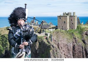 stock-photo-traditional-scottish-bagpiper-in-full-dress-code-at-dunnottar-castle-in-stonehaven-311284028
